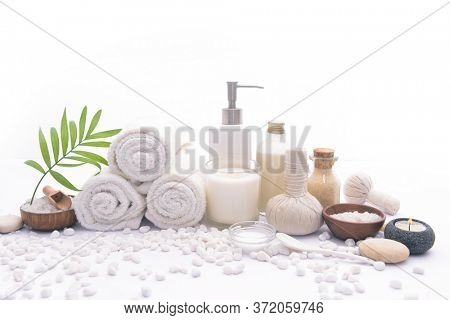 Spa setting with green palm leaves , bottles of essential oil l , herbal ball, frangipani,salt in bowl ,candle , herbal ,ball ,spoon on pile of white stones