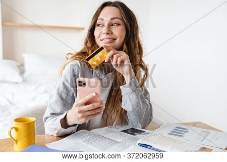 Photo of joyful student woman holding credit card and smartphone while doing homework in bedroom