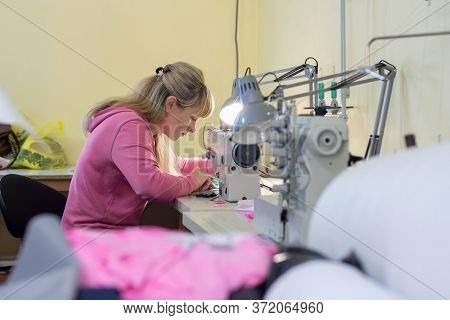 Worker In Sewing Workshop Sews On A Professional Sewing Machine