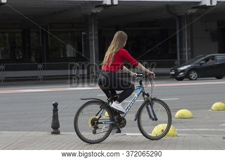 A Beautiful Girl Cyclist Rides Through The City Center, On The Streets Along The Sidewalk On A Bicyc