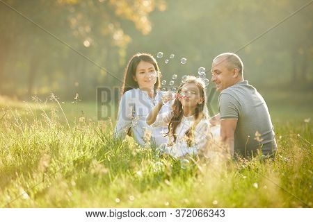 Happy Family With Child Girl Blow Soap Bubbles Outdoor In Sunny Summer Day