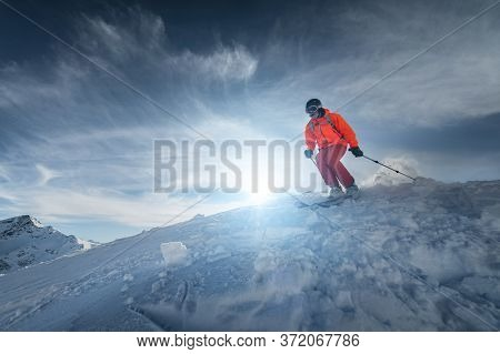 Skier Rides On A Snowy Slope On A Sunny Day At Sunset Against The Backdrop Of The Mountains. The Con