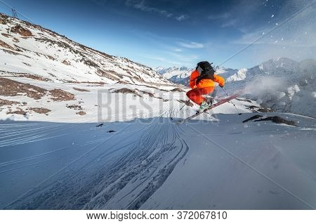 An Athlete Male Skier Jumps From A Snow-covered Slope Against The Backdrop Of A Mountain Landscape O