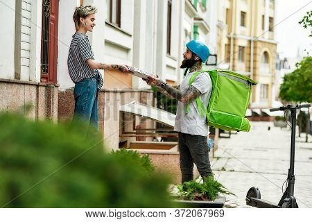 Bearded Delivery Man In Helmet With Thermo Backpack Giving Away Pizza To A Female Customer, While De