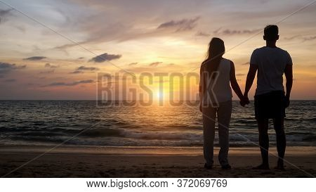 Silhouette Of Young People Walking On Beach To Boundless Ocean Water Joining Hands At Orange Sunset