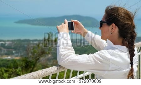 Brunette In White Blouse And Sunglasses Takes Photo Of Marvelous Cityscape And Endless Ocean With Sm