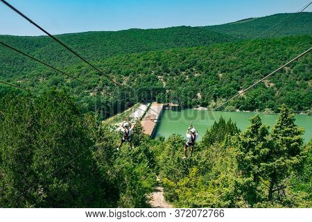 Two Guys Down A Cable In A Green Valley. Rope Descent With A Carbine Against The Backdrop Of A Huge