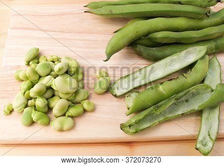 Freshly Picked Broad Beans Being Podded On A Wooden Board