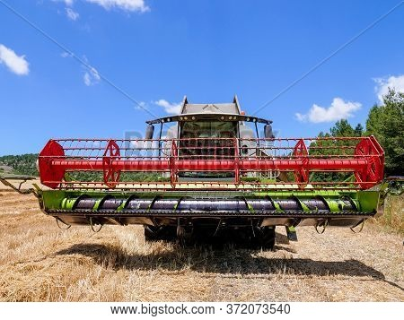 Combine Harvester Parked In A Large Wheat Field.