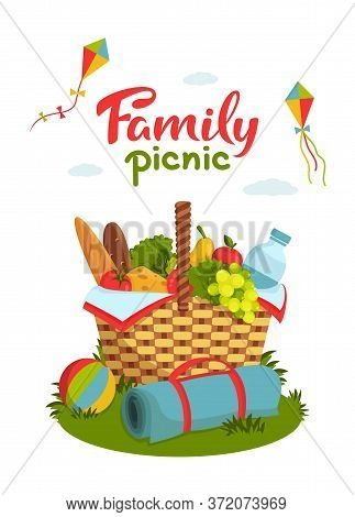 Family Picnic Concept. Wicker Picnic Basket Full Of Healthy Food, Picnic Blanket, Kites, Ball On Gra