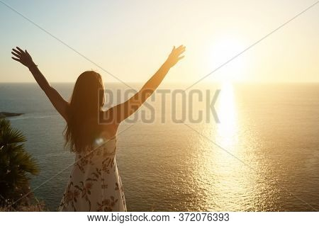Female Silhouette Raises Hands And Admires Pictorial Sunset Standing On Beach Edge At Sunset