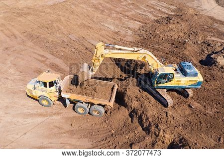 Excavator Loading Soil Onto An Articulated Hauler Truck
