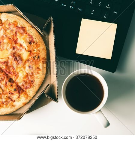 Pizza In Box, Cup Of Coffee, Laptop And Empty Sticker With Copy Space On Desk In Office. Concept Of
