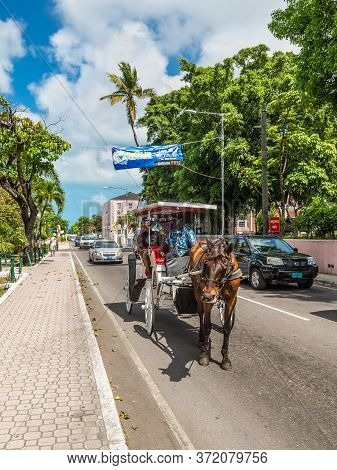 Nassau, Bahamas - May 3, 2019: Street View Of Nassau At Day With Tourists In A Horse Drawn Carriage