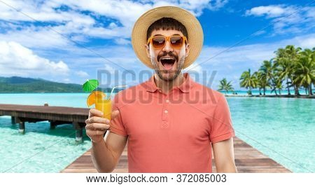 summer holidays, vacation and travel concept - happy smiling young man in sunglasses and straw hat with orange juice cocktail over wooden bridge on tropical beach background in french polynesia