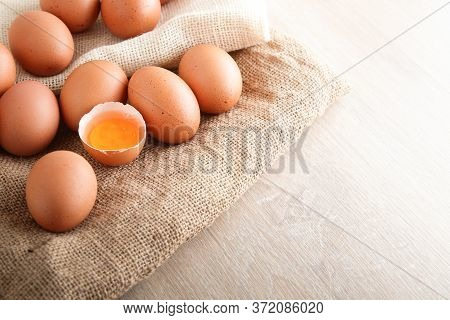 Many Organic Chicken Eggs Are Placed On A Brown Cloth And There Is A Yolk In The Middle. Is A Food T