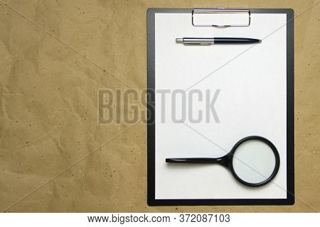 A Tablet With A White Sheet Of A4 Format With Magnifier, Pen And Magnifier On A Beige Craft Paper. C