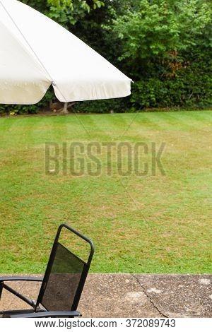 Patio Garden Umbrella And Chair By The Lawn Of A Home Garden