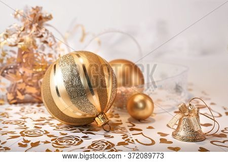 Shiny Sparkling Golden Christmas Baubles And Trinkets On Light Background. Traditional Shiny Golden