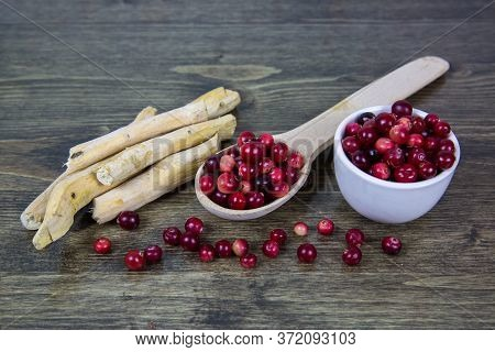 Cranberries In A Wooden Spoon, A White Cup And Horseradish Roots Laid Out On A Wooden Table Of Brown