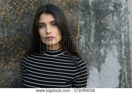 Frontal Portrait Of A Sensual Girl With Straight Brown Hair And Green Eyes Looking At Camera.
