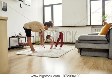 Full Length Shot Of African American Woman Baby Sitter And Caucasian Cute Little Girl Having Workout