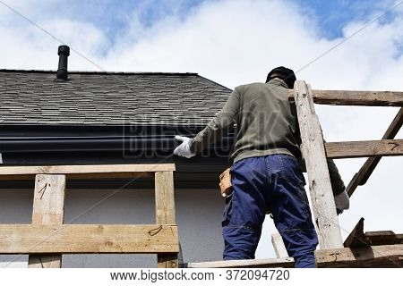 Construction Worker Installing Plastic Roof Rain Gutter Gray Shingles Roof With Wooden Eaves While S