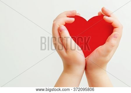 Closeup Of Hands Of Child Holding Paper Red Heart On White Background. Heart In Hands With Copy Spac