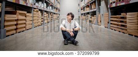 Asian Shopper Man Sitting Between Cardboard Box Shelves Aisle In Warehouse Choosing What To Buy. Sho