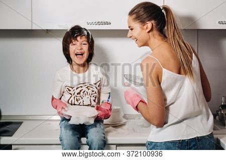 Housewife Mom In Pink Gloves Washes Dishes With Her Son By Hand In The Sink With Detergent. A Girl I