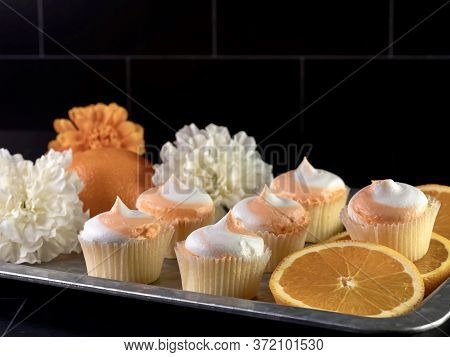 Rustic Metal Tray Filled With Fresh Orange Slices, Mini Orange Creamsicle Cupcakes With White And Or