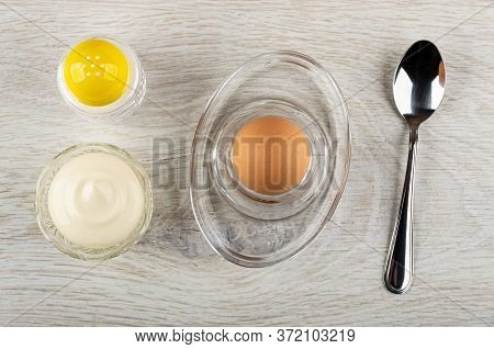 Salt Shaker, Transparent Bowl With Mayonnaise, Brown Unpeeled Egg On Glass Egg Stand, Teaspoon On Wo