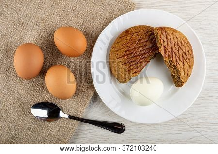 Brown Unpeeled Boiled Eggs, Teaspoon On Burlap, Peeled Egg And Broken Rye Bread In White Plate On Wo