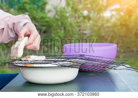 Preparation Of Ingredients For Frying Barbecue On A Metal Grill, A Male Hand Takes A Piece Of Meat I