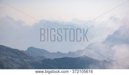 Beautiful Background With Blue Ridge In Hazy Mountains. Julian Alps