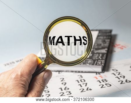 Maths Word Inscription Through Magnifier Glasson Book Of Maths On Blue Table And Calendar. Education