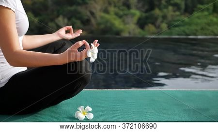 Young Woman Sits In A Lotus Position Near The Rooftop Pool Copyspace