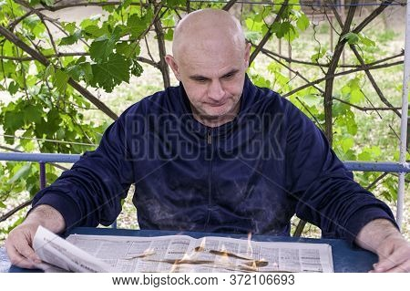 Hot News Concept A Man Reads A Burning Newspaper While Sitting In The Bower