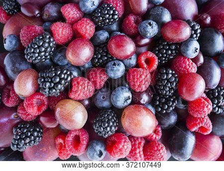 Background Of Fresh Vegetables And Fruits. Ripe Blackberries, Blueberries, Plums, Pink Grapes, Raspb