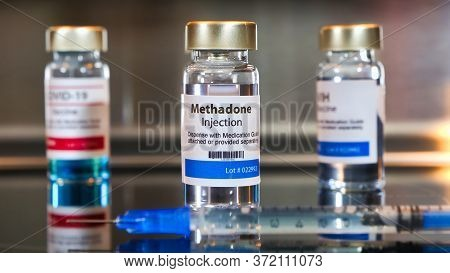 Vial Of  Methadone Injection With A Syringe On Black Table And Stainless Steel Background.