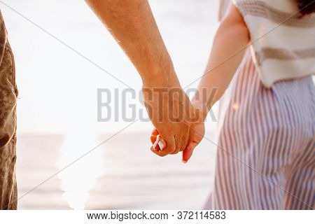 Couple Holding Hands At Sunset On Beach. Romantic Man And Woman Enjoying Sunset, Romance And Love By