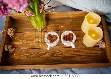 Two Cups Of Cappuccino, A Drawing Of A Heart On A Foam On An Old Wooden Tray. Overhangs On A Tray. S