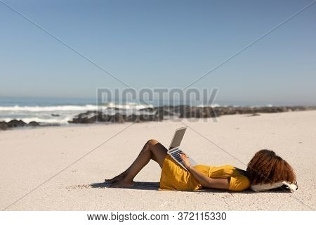 A happy, attractive mixed race woman enjoying free time on beach on a sunny day, wearing a yellow dress, lying on the sand, using her laptop, sun shining on her face.