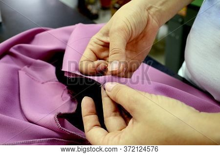 Seamstress Prepares Knitwear For Sewing Clothes. Female Hands With A Pin Stab Black And Pink Fabric