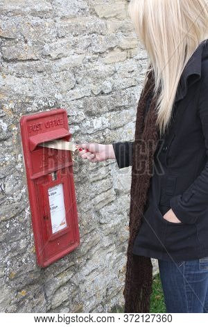 A Woman Posts A Letter In A Post Box In Witney, Oxfordshire In The Uk On 28th October 2008
