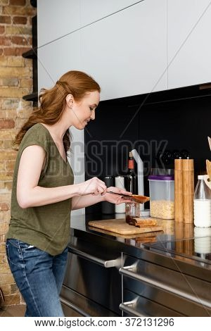 View Of Smiling Woman Pouring Sweet Jam On Toast Near Kitchen Worktop