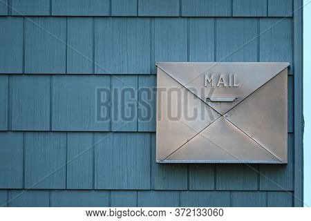 A Metal Mailbox On A Wall Of Blue Shingles.