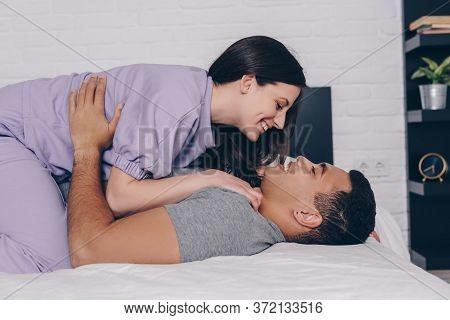 View Of Cheerful Woman Lying On Handsome Bi-racial Man In Bedroom