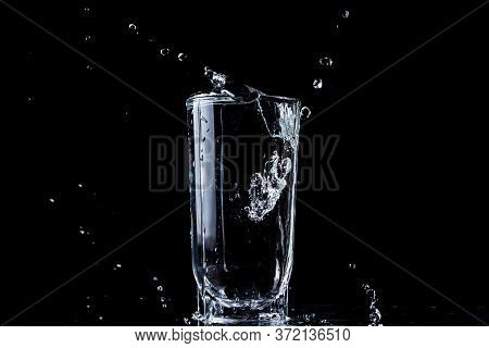 A Stream Of Water Pours Into A Glass Of Water. Water Overflows The Glass. Photo On A Black Backgroun