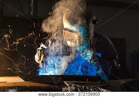 Electric Welder Working With Argon Welding, A Welder Wearing A Mask While Working On Detail